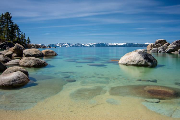 view of lake tahoe with turqoise waters, rock formations and snowcapped mountains in background